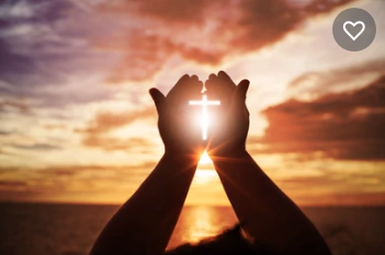 Cross of light shining through cupped hands in front of a setting sun